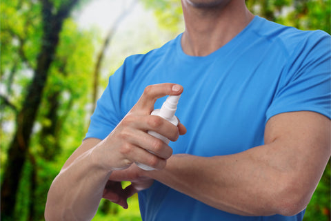 Male using insect repellent spray from bootle in forest