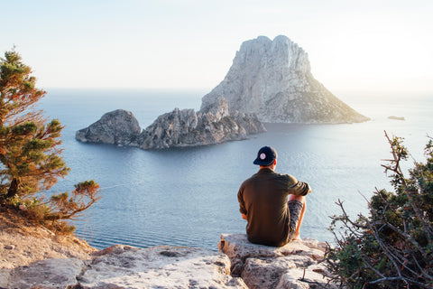 man relaxing outdoors with a view of the water and taking advantage of the benefits of ashwagandha for stress relief and relaxation