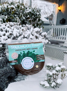 Packaging of Chocolate Mint Cookie being held up by a hand with snow in the background