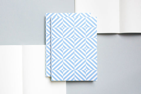 A5 notebook with ruled pages and an embossed cover printed in blue