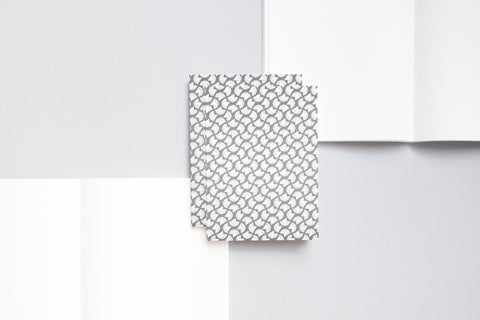 A6 notebook with plain pages and an embossed cover printed in grey