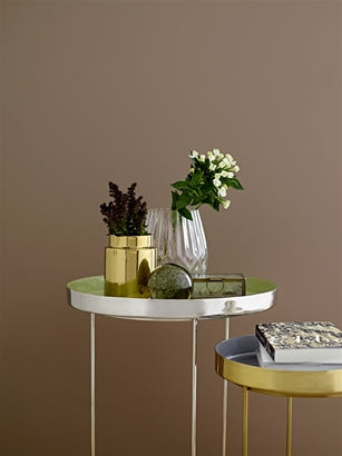 Gold stoneware vase displayed on a small side table with clear glass vase and books