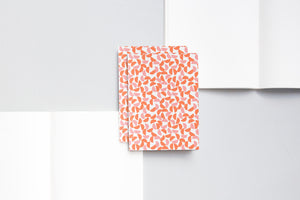 A6 notebook with plain pages and an embossed cover printed in red