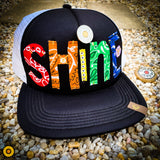 "SHiNE dot the ""i"" with a token"