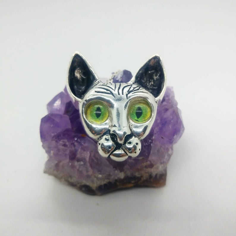silver cat pendant with glass cat eyes