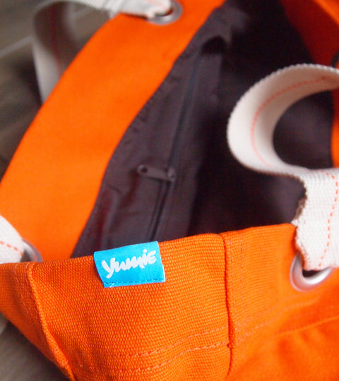Orange canvas tote bag with chocolate colored interior and yumie logo tag