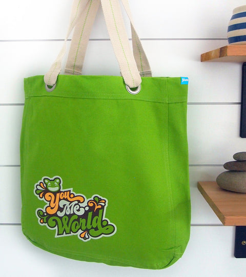 Lime green yumie brand canvas tote bag hanging near decorative shelves