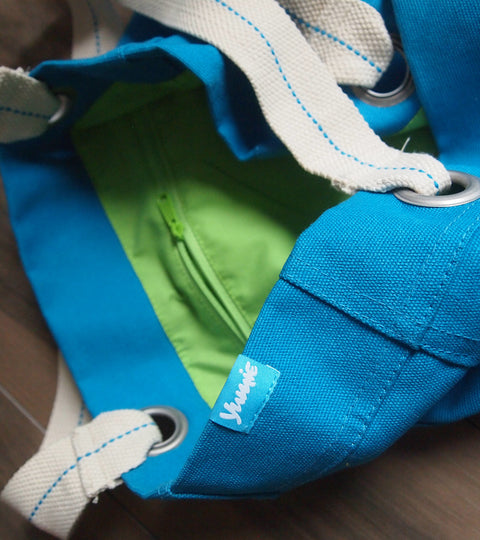 Turquoise tote bag interior with lime green zipper pocket showing yumie logo tag