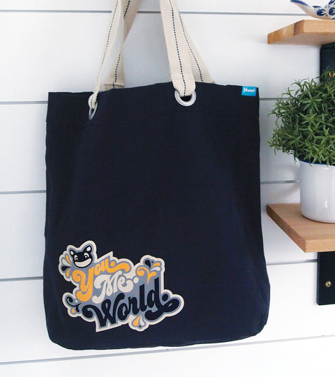 Navy canvas shopping tote bag with seventies logo graphic hanging on decorative hook