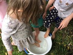 A group of children enjoy water play - Snail Mail Stories inspires children to play and learn in nature