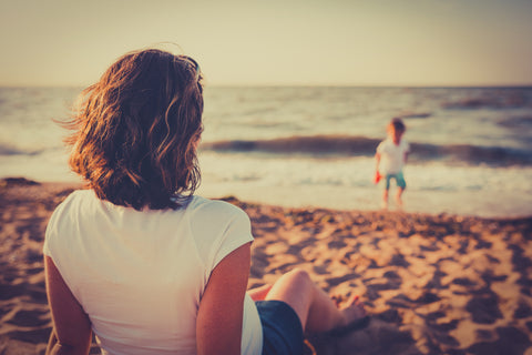 Parent sits back on a beach to watch her child play freely - Slow Parenting