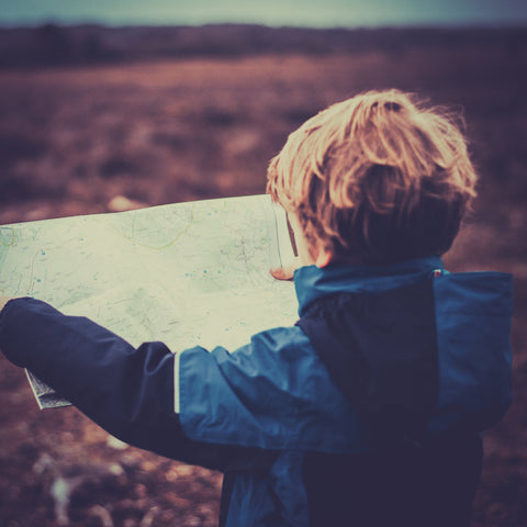 Little boys explores a map - Helicopter Parenting does not give kids the space they need to work things out for themselves
