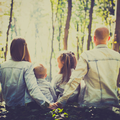 A family slowing down to sit in nature and spend quality time together  - a Slow Parenting approach