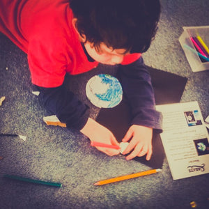 A little boy enjoys creating the educational craft his snail mail stories pen pal sent him this month