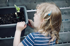 A young girl appreciates a plant - Snail Mail Stories teaches children to respect nature.