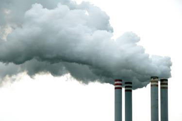A picture containing industrial smokestacks, industrial chimneys, air pollution, steam, emission, white smoke