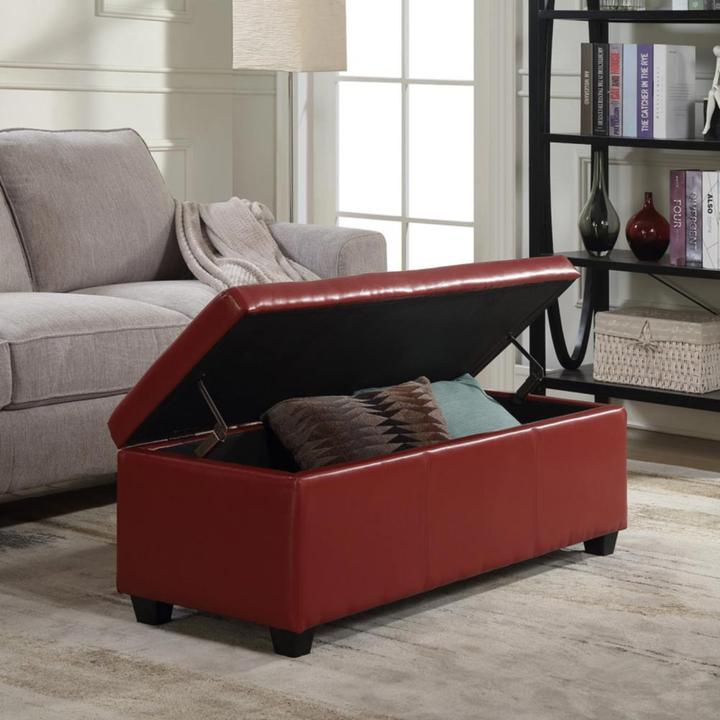 Red ottoman opening to reveal blankets inside multifunctional furniture