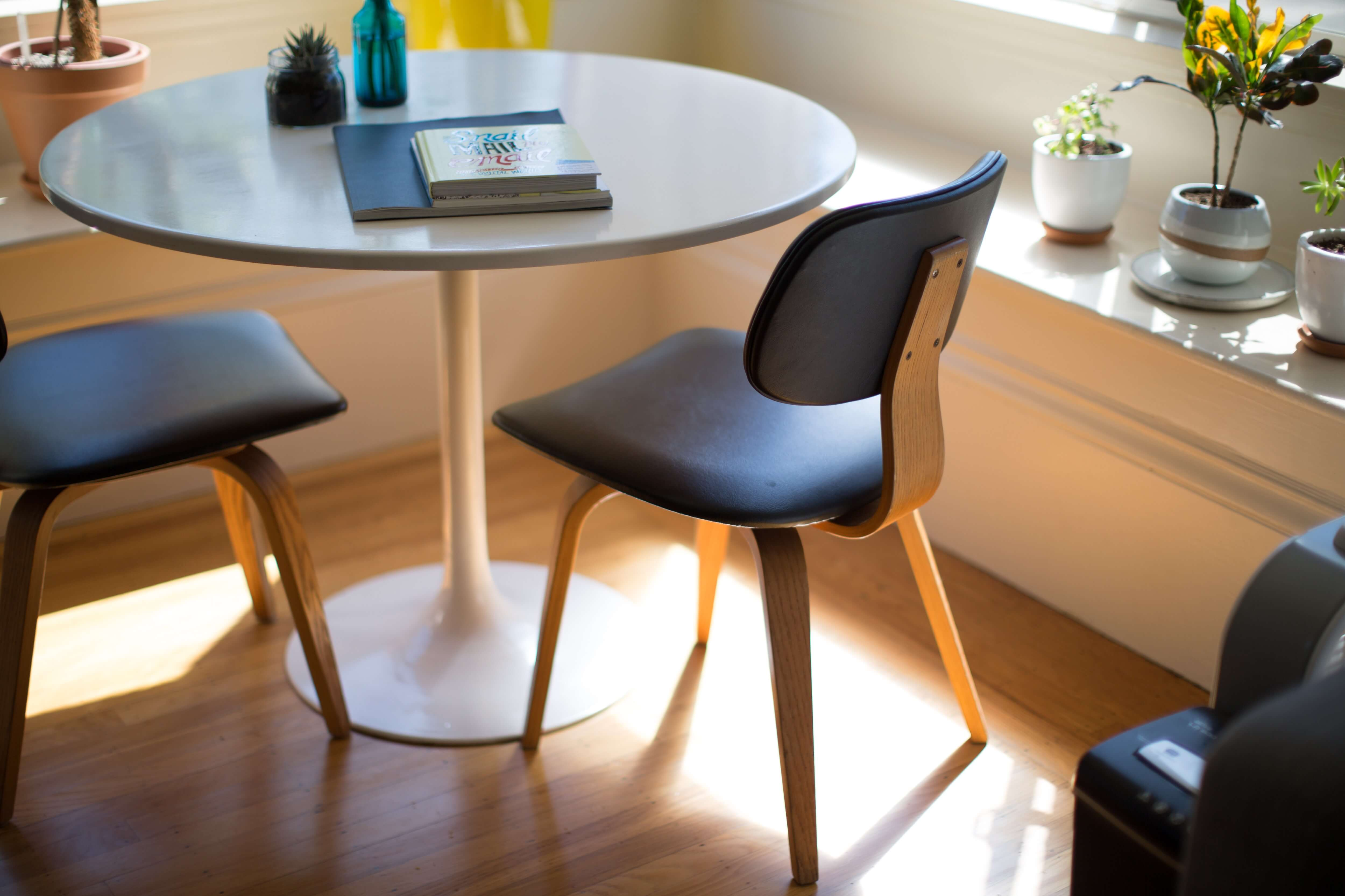 Round white table with two chairs on brown wooden floor
