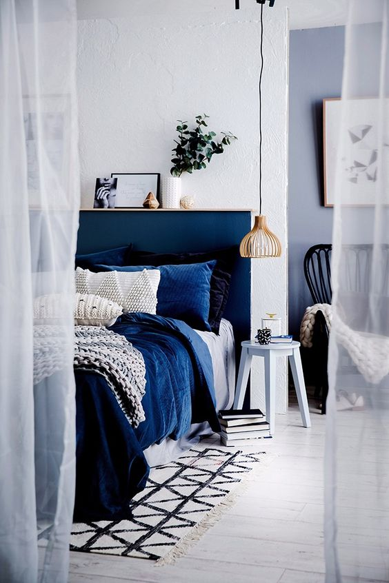 indigo blue headboard with blue pillows in a room with a hanging pendant light