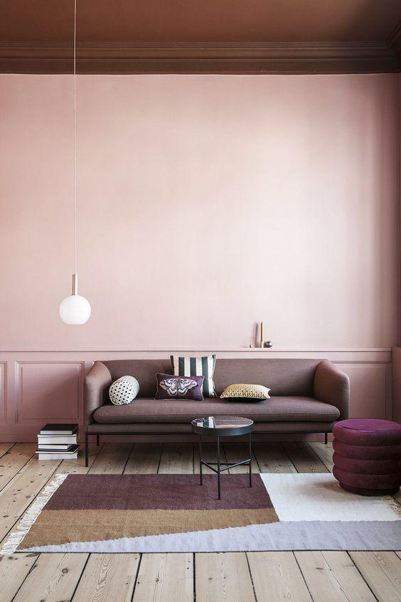 light brown couch set against a Millennial pink wall and a geometric area rug
