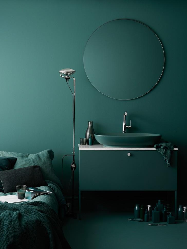 Dark teal themed room with mirror, cabinet, and sink