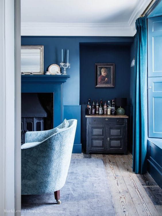 denim blue room with accent armchair and a wooden floor