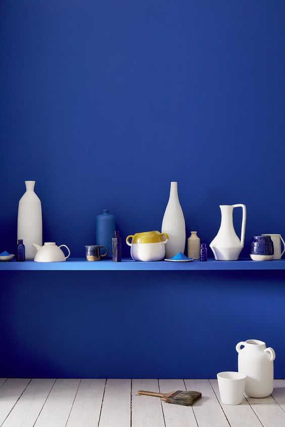 electric blue shelf and wall with various vases and pots on top
