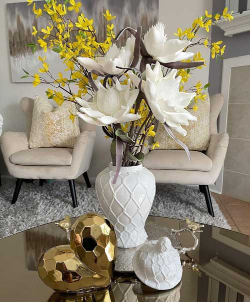 gold heart decoration on glass table next to white vase with white and yellow flowers