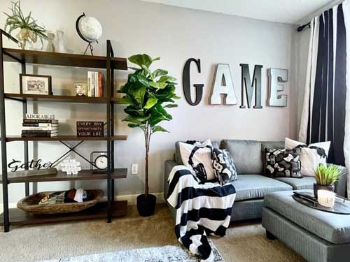 living room setting featuring a large book case, gray couch and ottoman with a black and white striped blanket