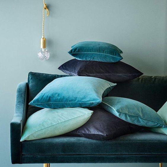 Pile of velvet scatter cushions on a couch in various shades of blue