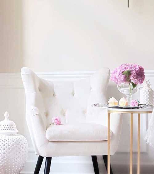 white accent chair next to side table with pink flowers and cupcakes