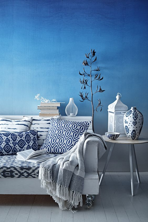 white couch with blue and white pillows against a blue wall