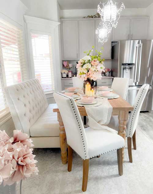 white dining room cushioned bench and chairs with table set for valentine's day