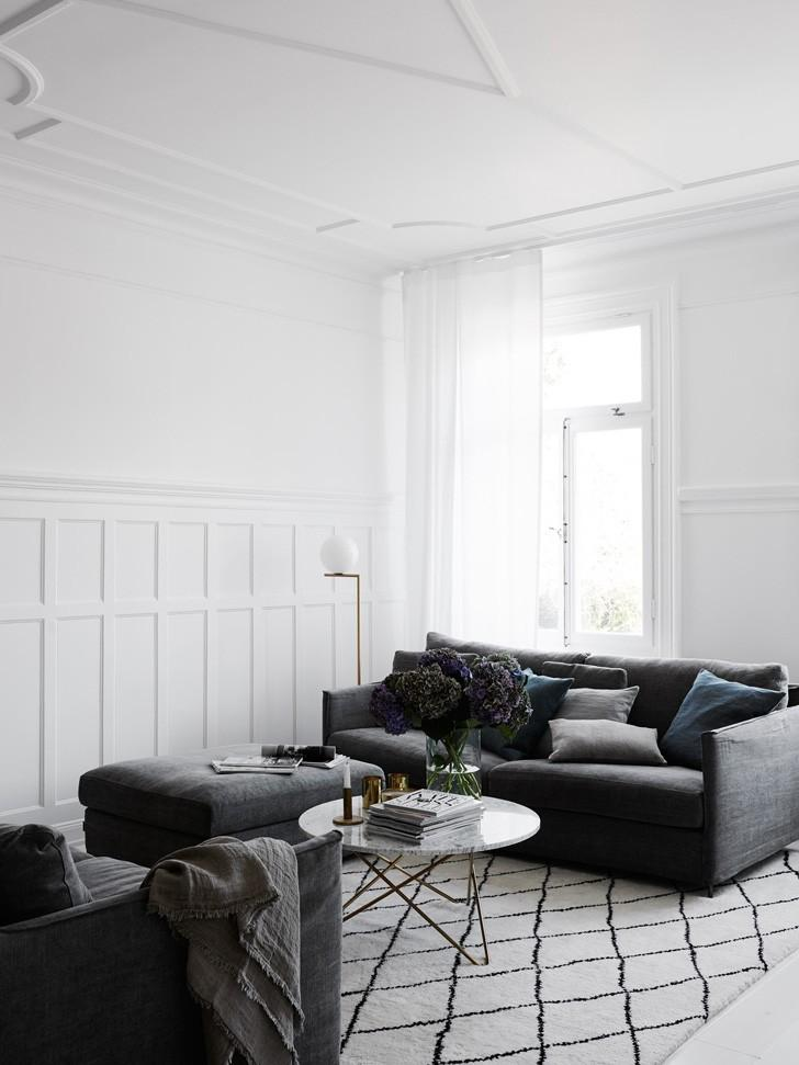 White living room with dark gray couch, ottoman, glass coffee table, and black and white geometric area rug