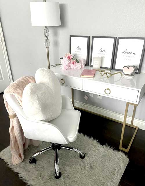 white office desk with gold finishes paired with white office chair and white heart-shaped pillow