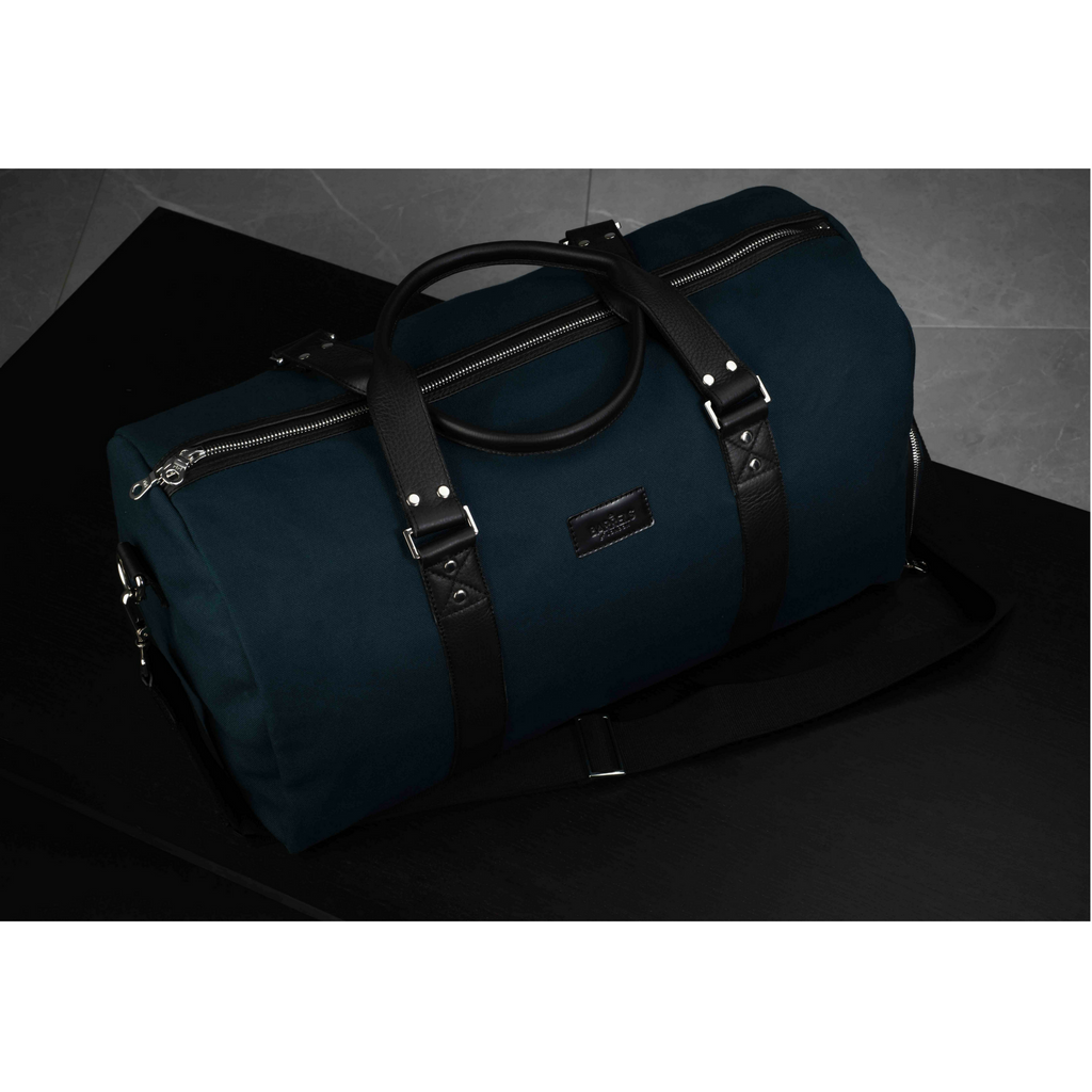 Dark view of a Mayfair barrel bag finished in blue and black. Barrels of London.