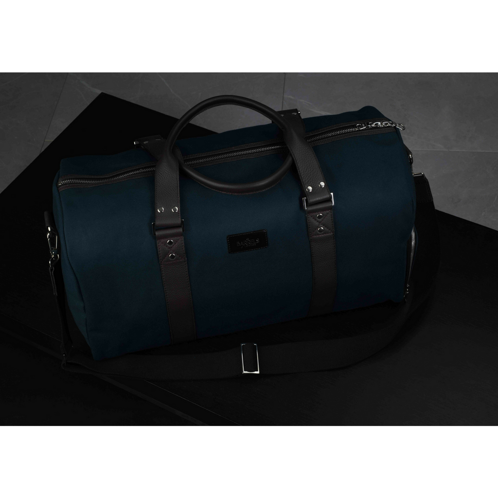 Dark view of a Mayfair barrel bag finished in blue and brown. Barrels of London.