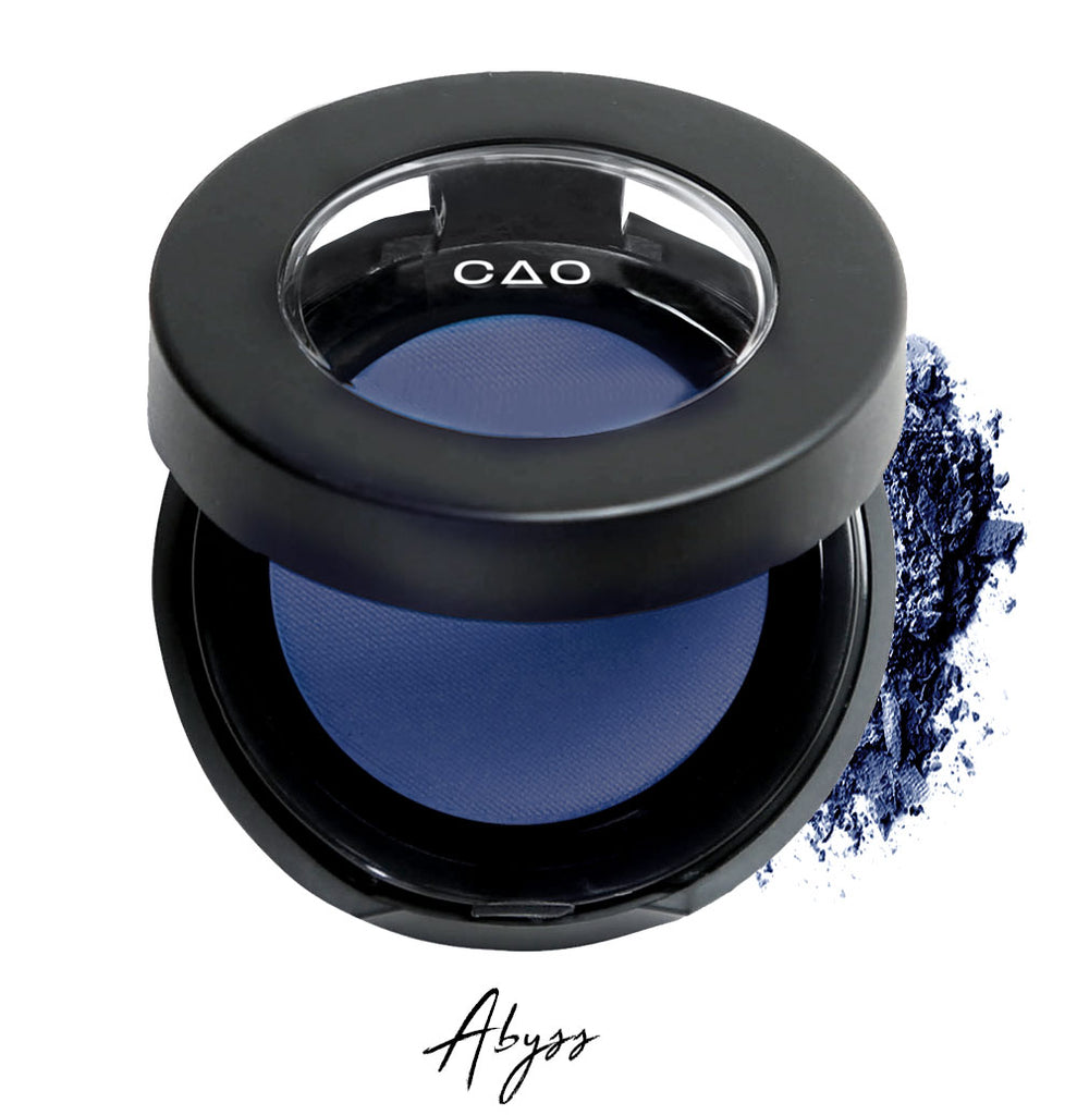 "Semi- open eyeshadow compact with blue compressed eyeshadow in shade ""Abyss""powder and on white background with loose eyeshadow powder on white.."