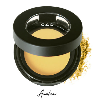 "Semi- open eyeshadow compact with yellow eyeshadow in shade ""Awaken"" compressed powder and on white background with loose eyeshadow powder on white.."