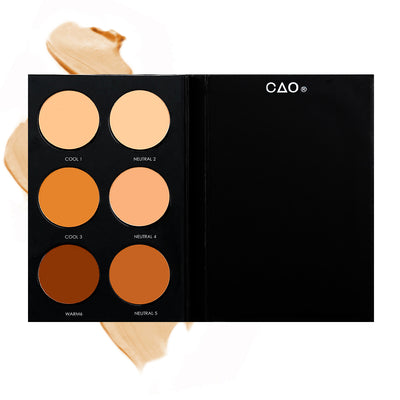 "Black Matte rectangular cardboard palette with 6 circular openings for ""Advanced Foundation"" refill cream product in shades Cool 1, Neutral 2, Cool 3, Neutral 4, Warm 6, and Neutral 5, on top of creamy swatch."