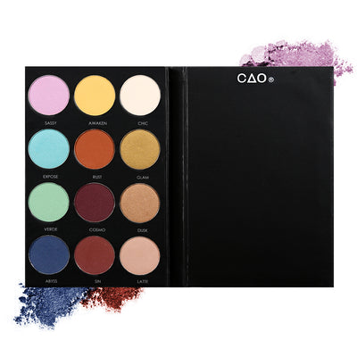 Black eyeshadow pallete with 12 shades of circular compressed eyeshadows. From left to right, First row: pink, light yellow, cream. Second Row: teal rust, mustard, third row: seafoam, burgundy, light brown. Last Row: dark blue, rust, light nude.