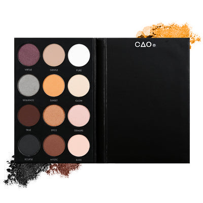 Black eyeshadow pallete with 12 shades of circular compressed eyeshadows. From left to right, First row:mauve, light brown, white. Second Row: grey, light orange, cream. Third row: dark brown, light brown, light pink. Last Row: charcoal, warm brown, light peach
