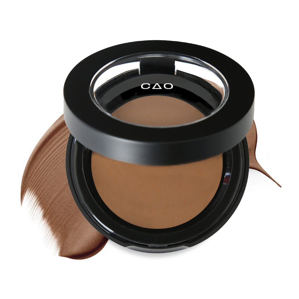 "Round Matte Black Component, clear round top window, filled with round creamyfoundation product shade in ""Cool 6"" on top of creamy swatch."