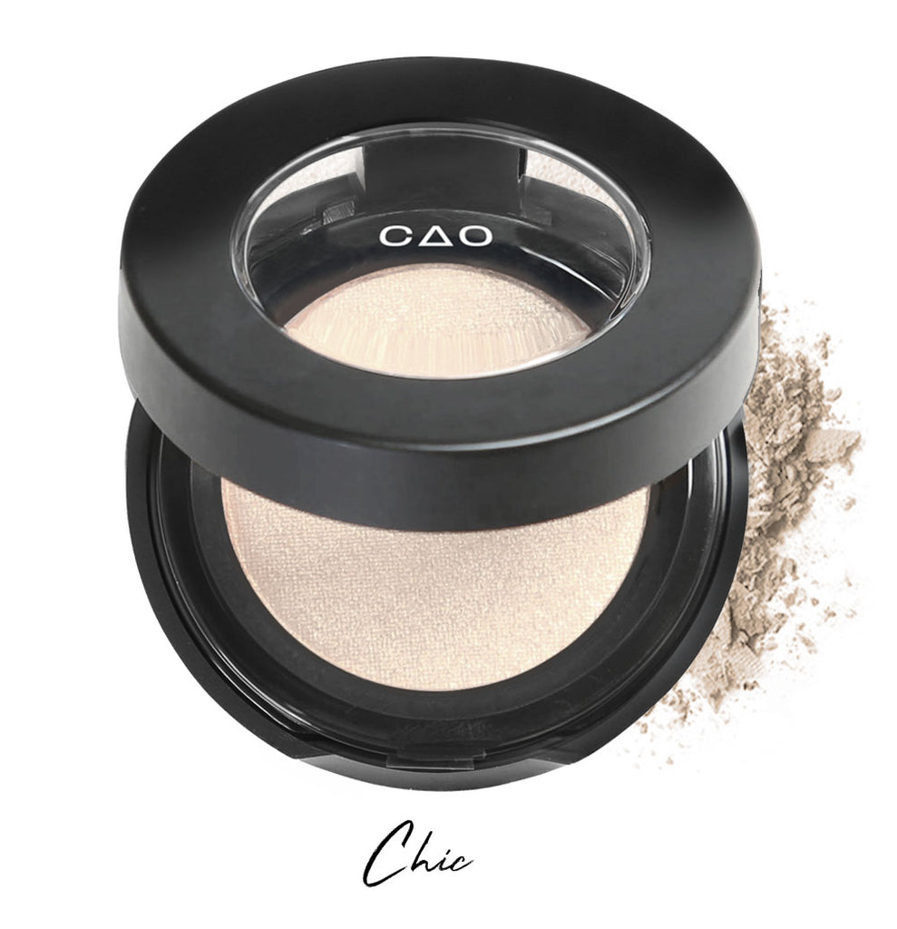 "Semi- open eyeshadow compact with almond milk colored eyeshadow in shade ""chic"" compressed powder and on white background with loose eyeshadow powder on white.."