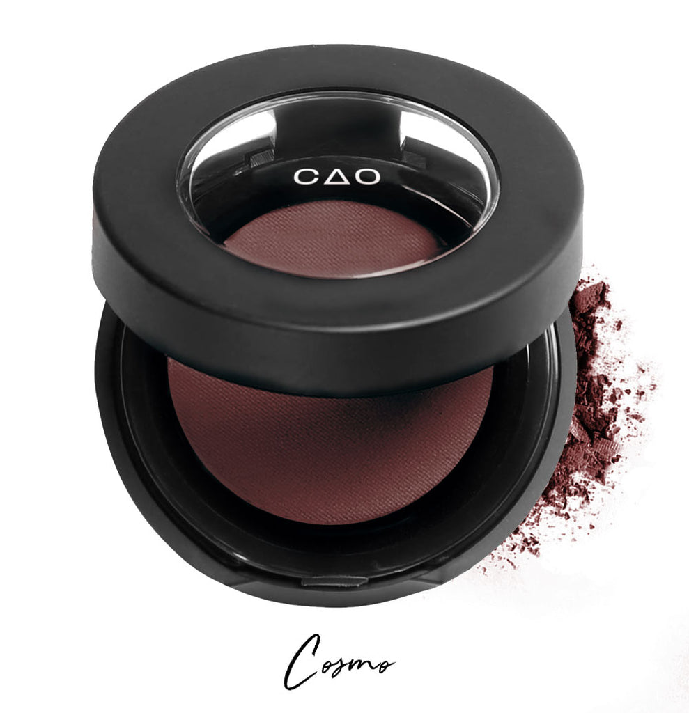 "Semi- open eyeshadow compact with dark burgundy eyeshadow in shade ""Cosmo"" compressed powder and on white background with loose eyeshadow powder on white.."