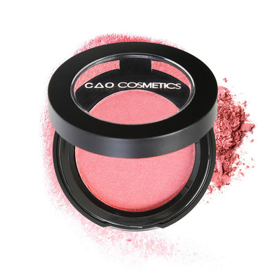 "Round Matte Black Component, clear round top window, filled with compressed round powder blush shade in ""Delicious"" on top of loose powder swatch."