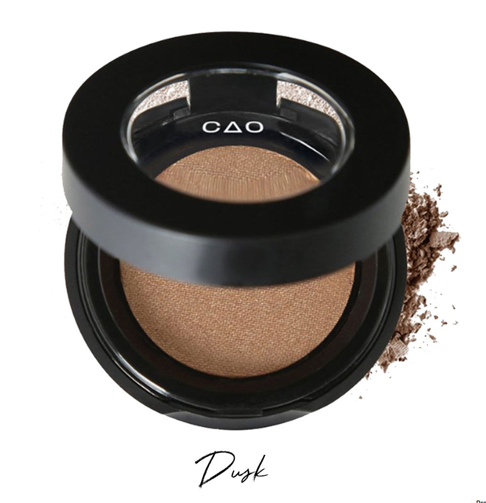 "Semi- open eyeshadow compact with light brown eyeshadow in shade ""Dusk"" compressed powder and on white background with loose eyeshadow powder on white.."