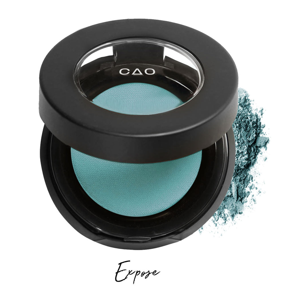"Semi- open eyeshadow compact with teal eyeshadow in shade ""expose"" compressed powder and on white background with loose eyeshadow powder on white.."