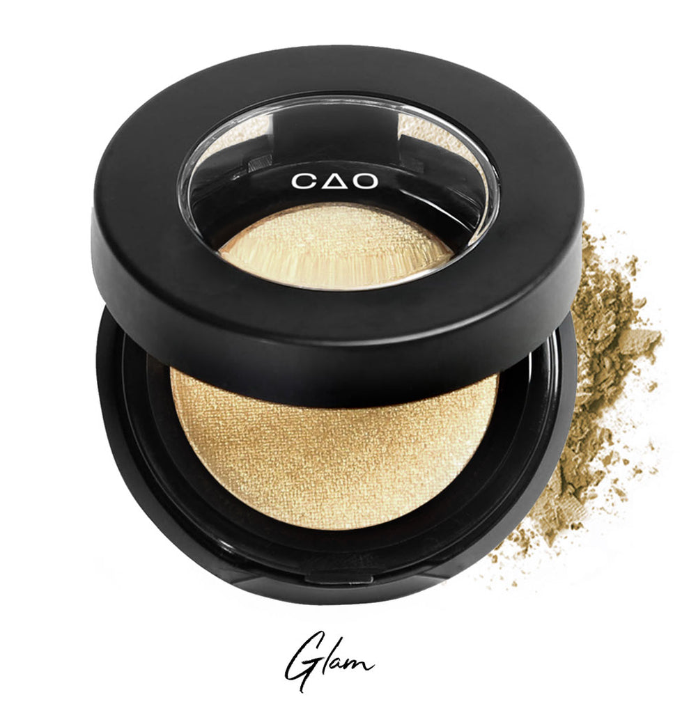 "Semi- open eyeshadow compact with light shimmer gold eyeshadow in shade ""glam"" compressed powder and on white background with loose eyeshadow powder on white.."