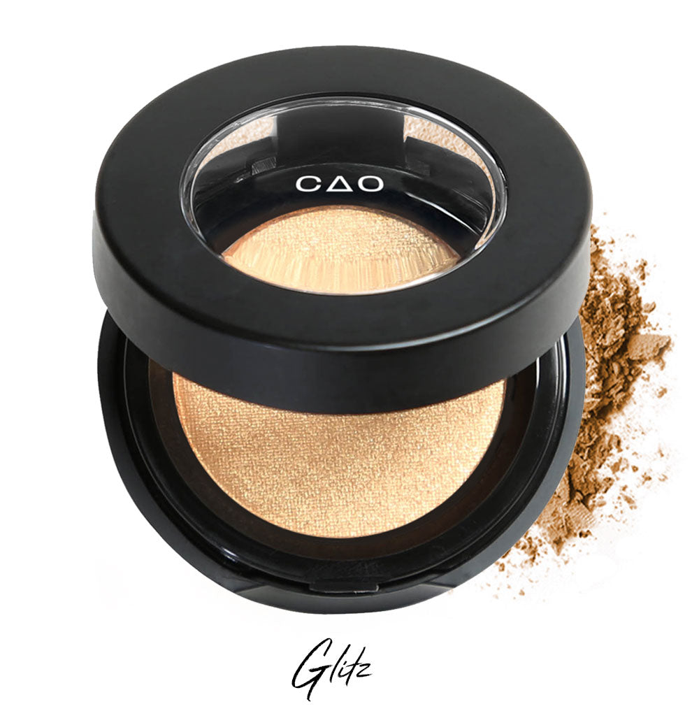 "Semi- open eyeshadow compact with shimmer warm gold eyeshadow in shade ""Glitz"" compressed powder and on white background with loose eyeshadow powder on white.."